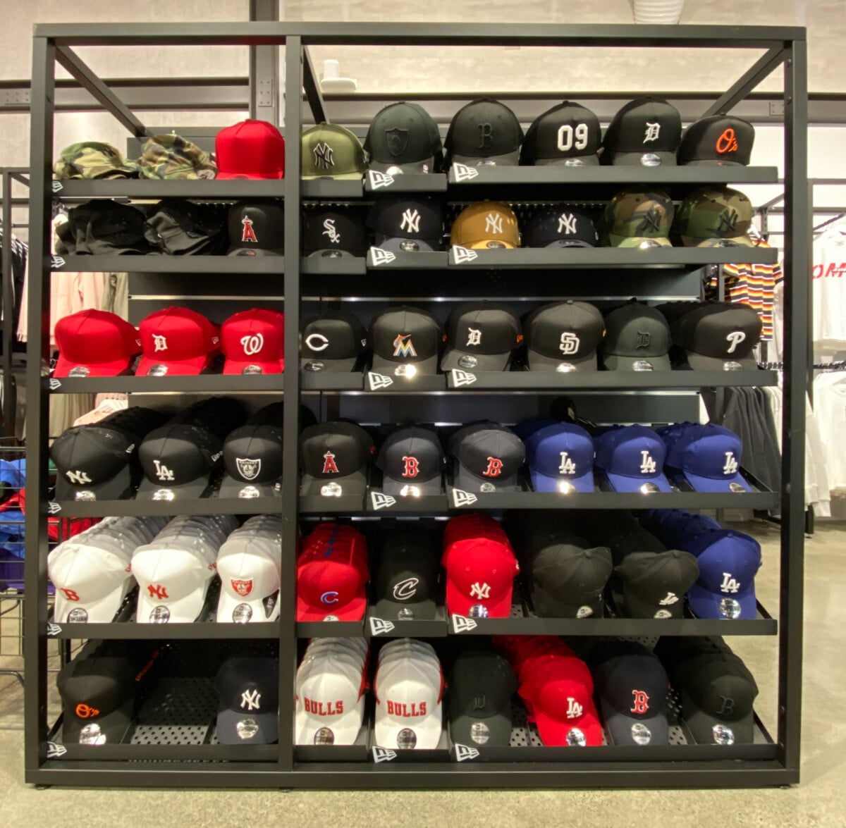 Large metal framed hat display stand with angled mesh shelves