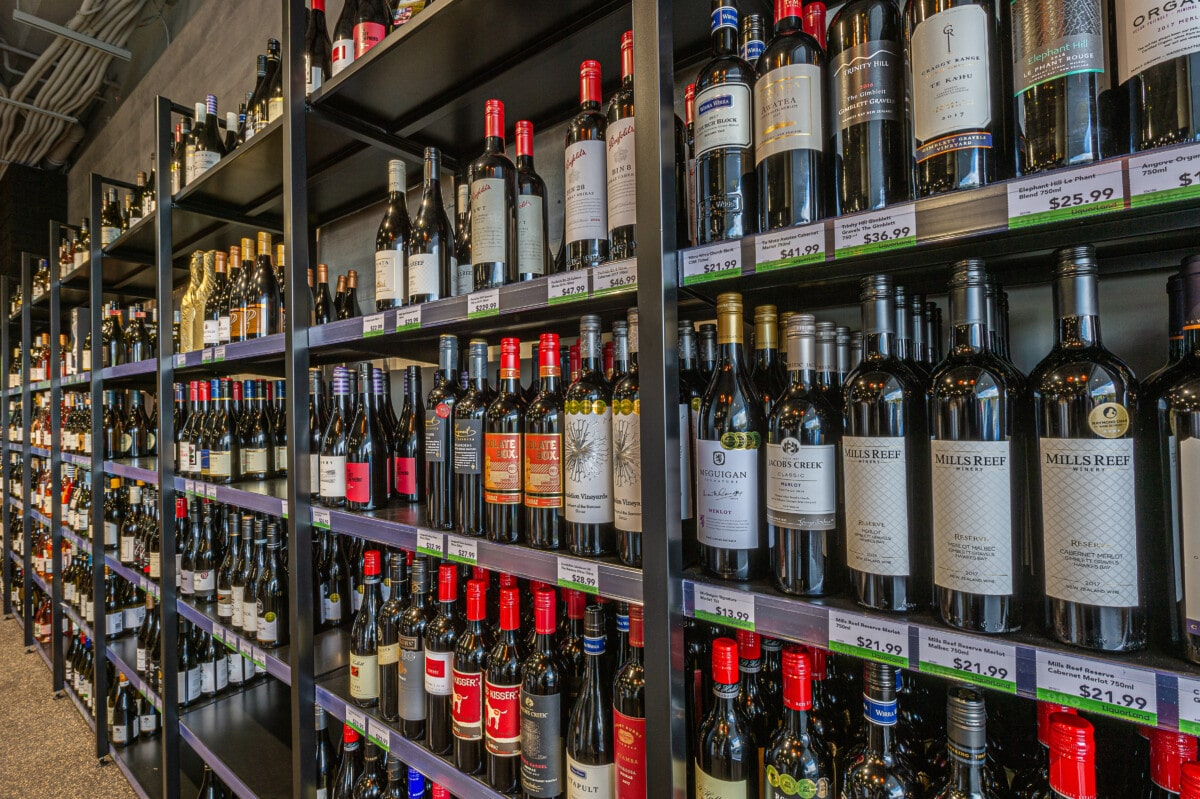 Liquor store wall system with outrigger posts and adjustable height shelving