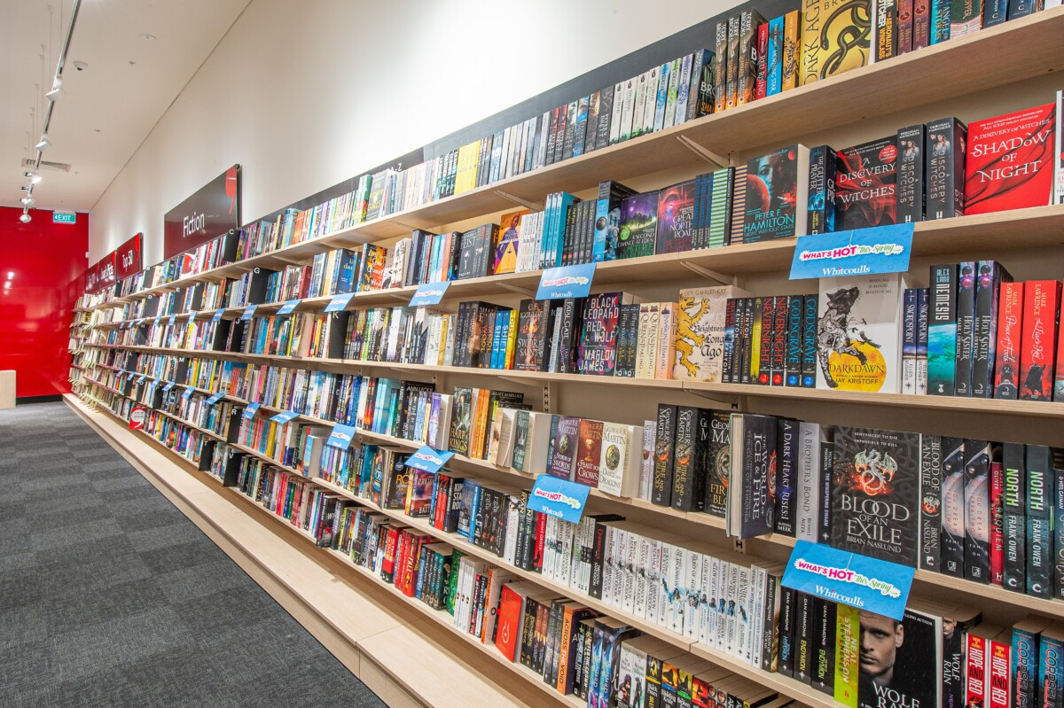 Book store wall system with metal slotted posts supporting adjustable height brackets for the joinery shelves