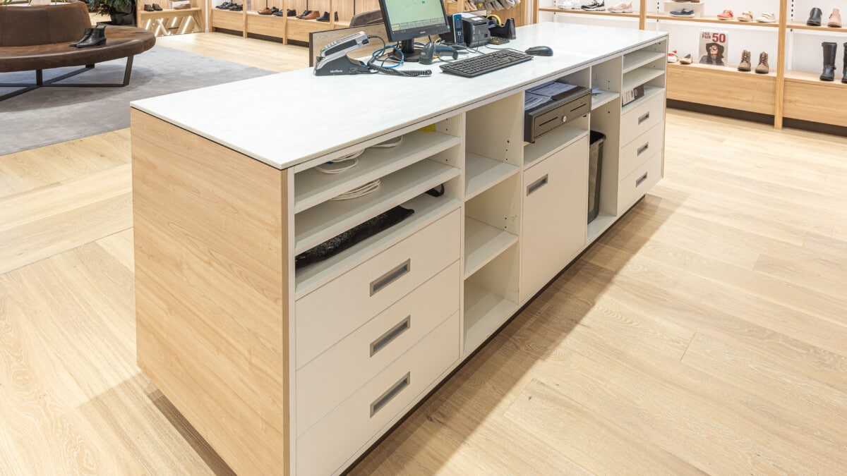 Back of service counter showing cashdrawer, shelving and storage