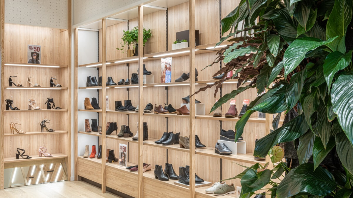 Footwear store wall system with woodgrain infill panels in between slotted metal posts supporting the woodgrain shelf brackets and shelves