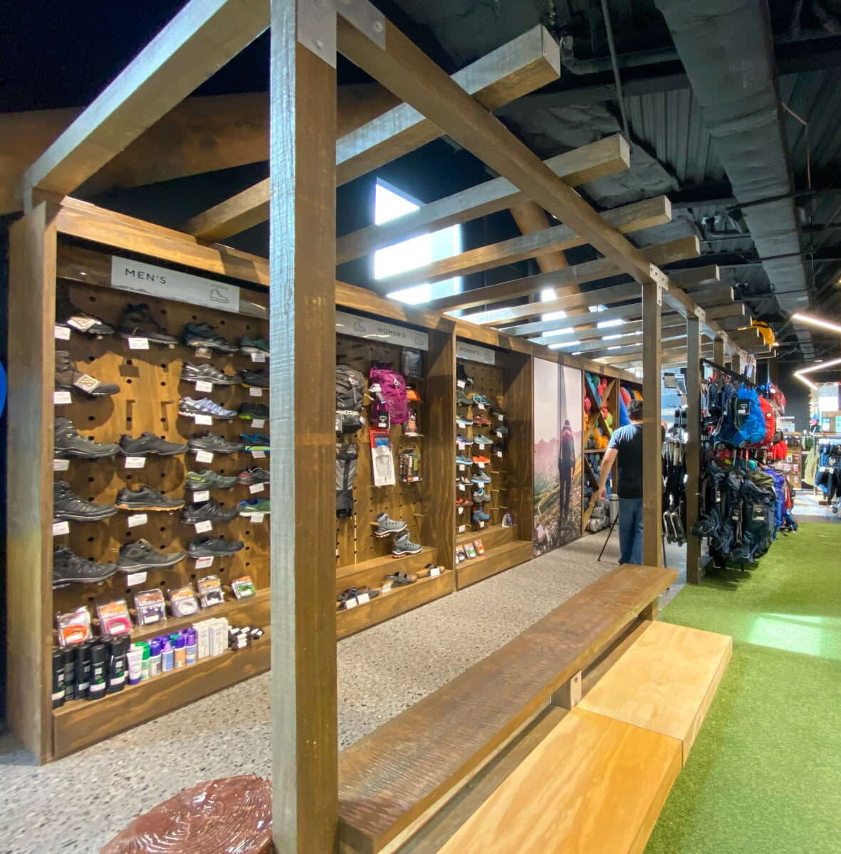 Freestanding footwear wall with puck display and seating made with natural wood and plywood